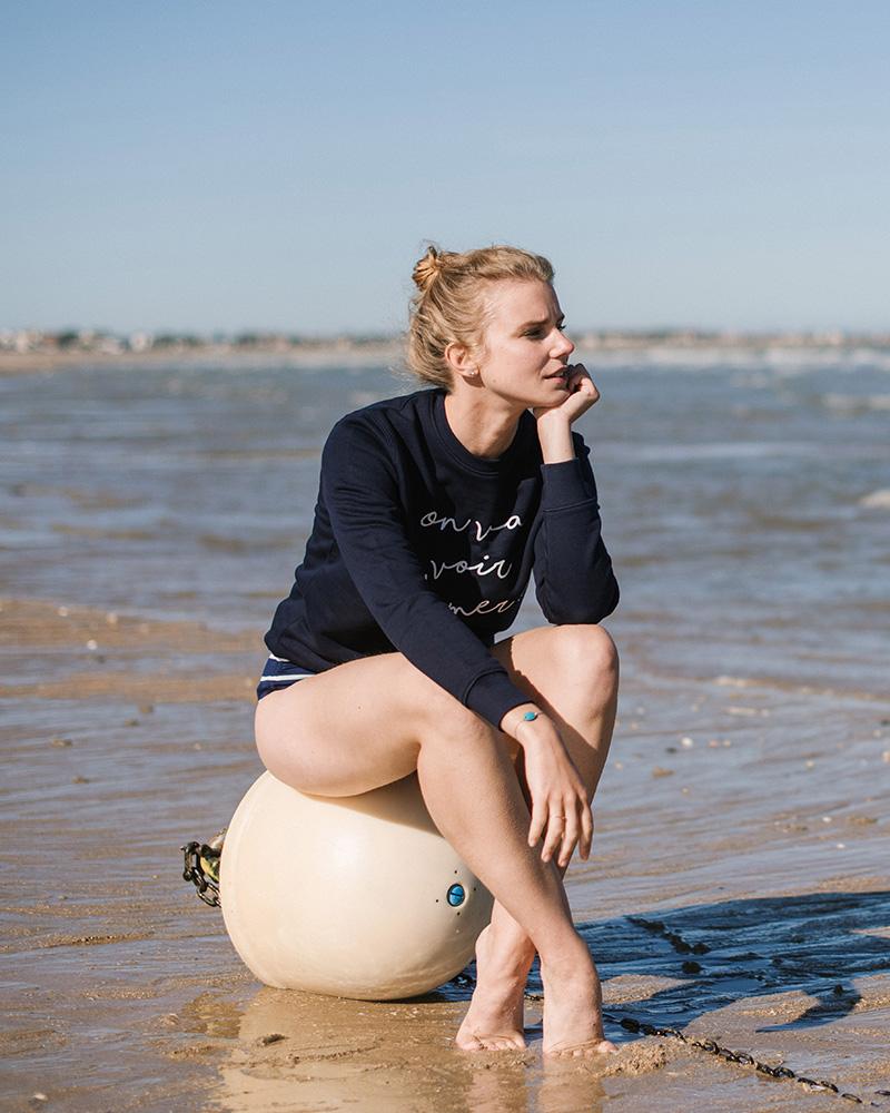 femme sur la plage avec sweatshirt a message